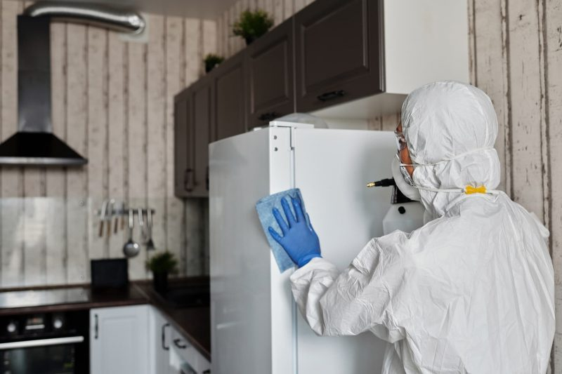 person-in-a-protective-suit-disinfecting-inside-the